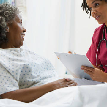 Nurse reviewing chart with patient at bedside