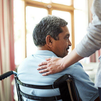 Man in wheelchair with caregiver's hand on his back.