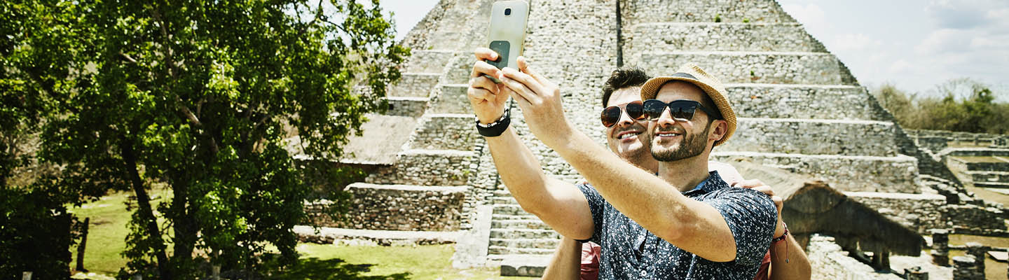 2 smiling men taking selfie at Mayapan ruins