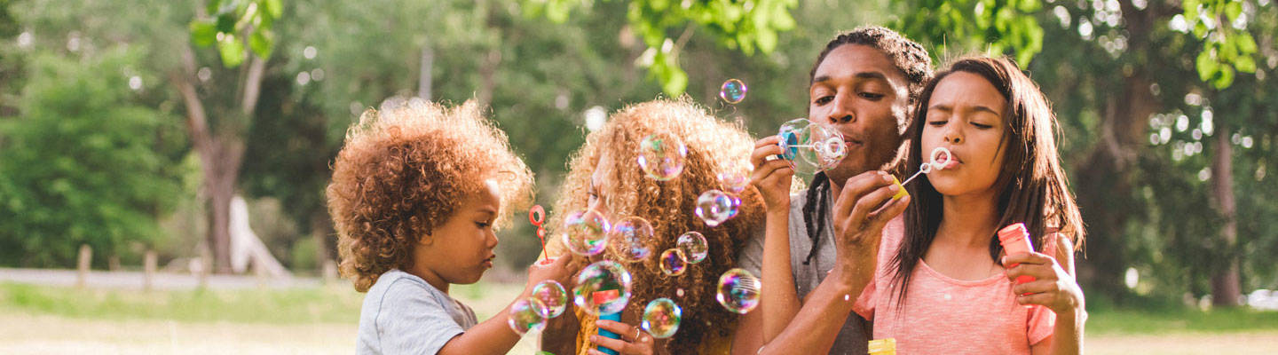 family-at-park-blowing-bubbles