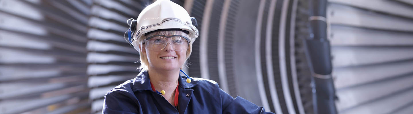 Female engineer in front of turbine