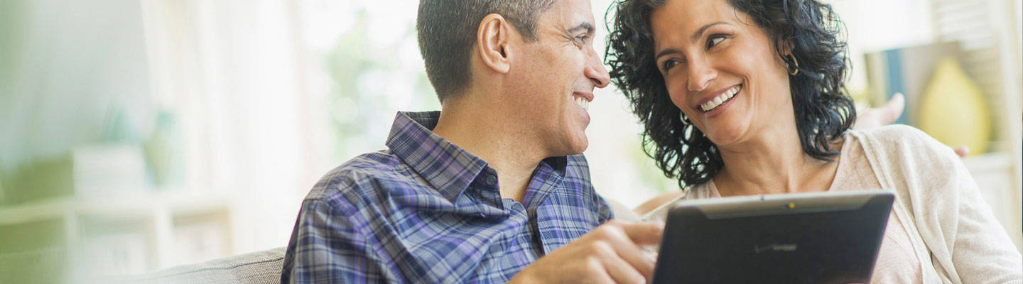 Middle aged couple looking at tablet and smiling