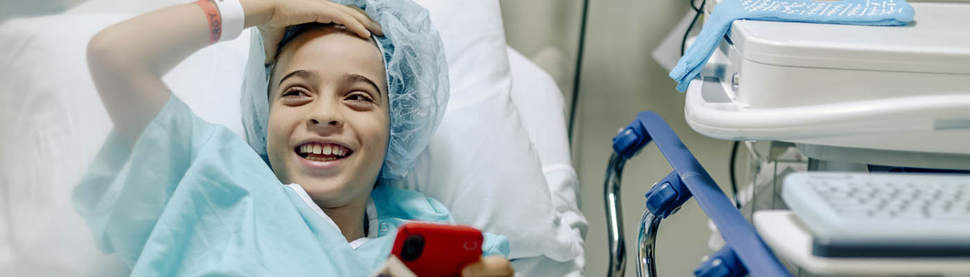 Laughing kid in a hospital bed