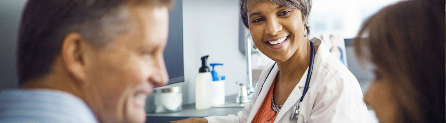 Smiling doctor conversing with patient