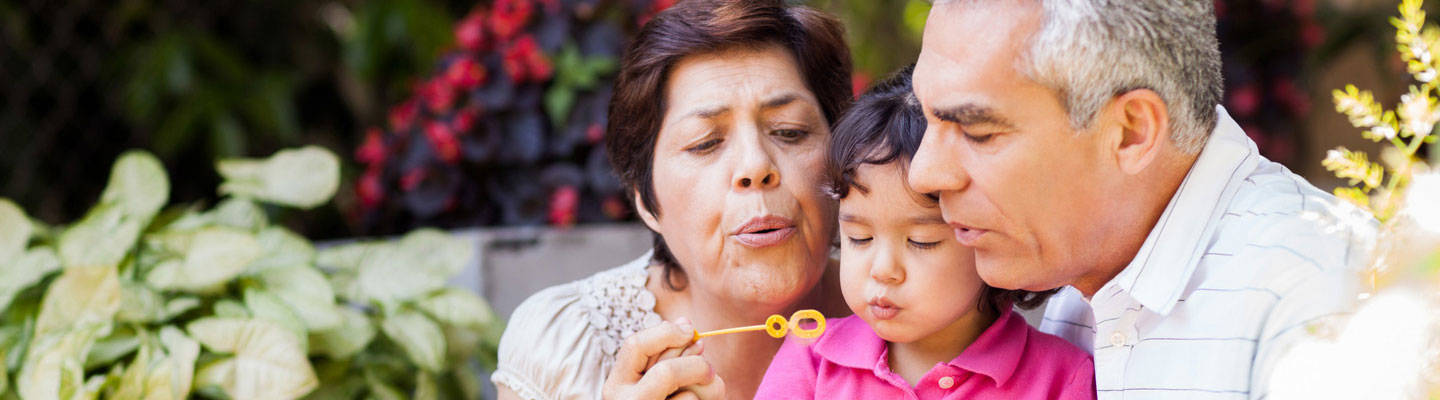 Grandparents blowing bubbles outside with their grandchild.