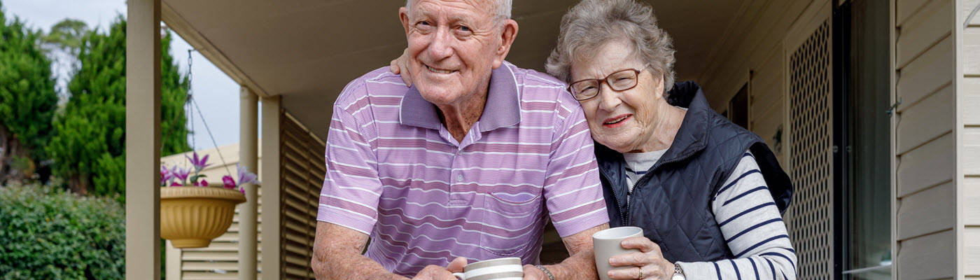 Elderly couple drinking coffee on their porch