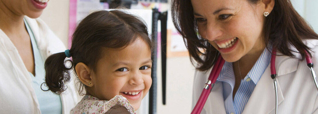 Doctor smiling at young girl during check-up