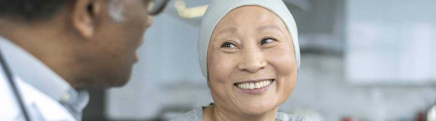 Asian woman with cancer talking to doctor