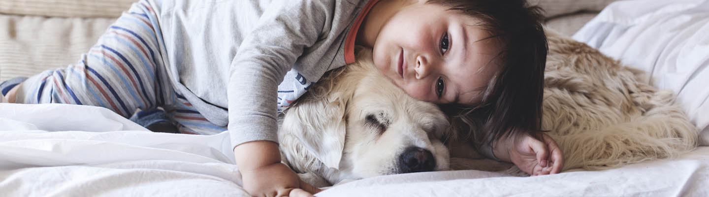 Young boy cuddling with dog