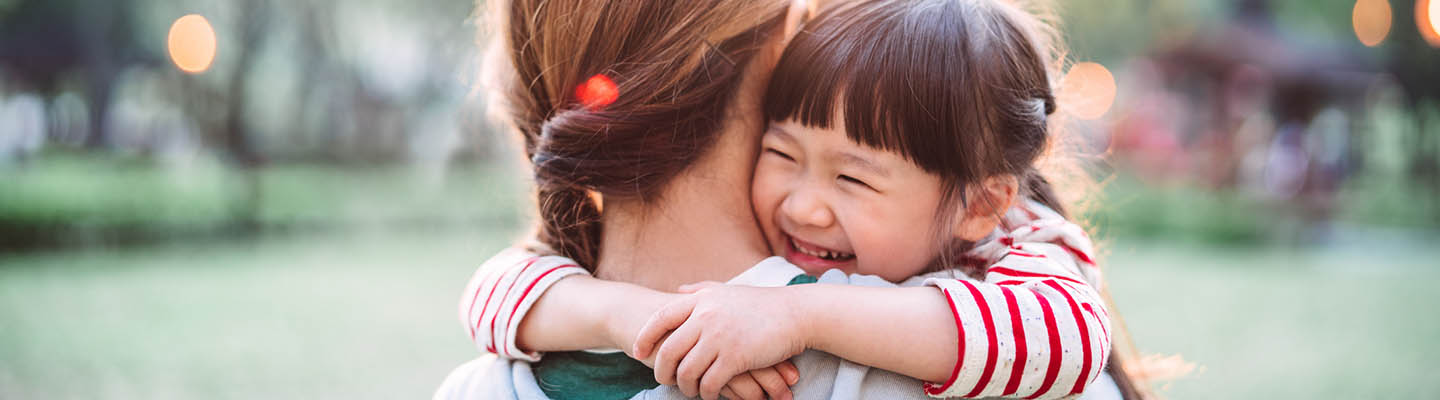 Young girl smiling while mother carries her