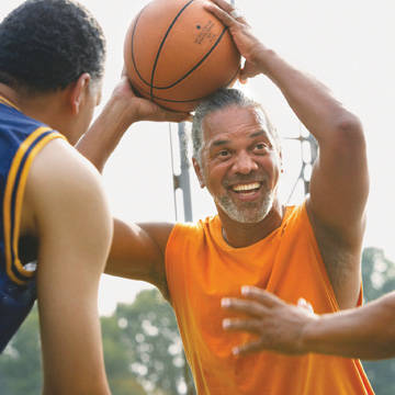 Older man playing basketball with friends