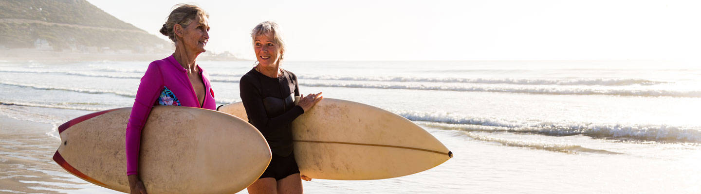Two senior women carrying surfboards on the beach