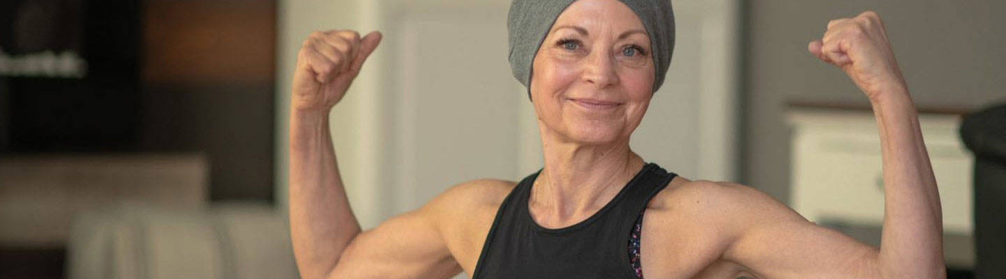 Female cancer patient flexing bicep muscles